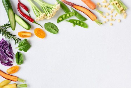 Food background border frame of colorful fresh produce raw vegetables, corn carrot chilli cucumber purple cabbage spinach rosemary herb, plenty of copy-space