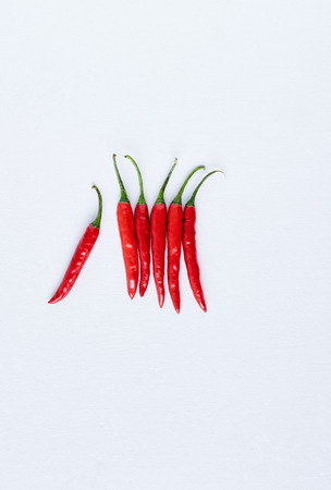 odd one out: Food background of bunch of fresh hot spicy birds eye chillis on white background, with one sticking out odd one out, plenty of copy space Stock Photo