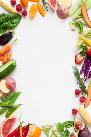 Food background border frame flatlay overhead of colorful fresh produce raw vegetables, carrot chilli cucumber purple cabbage spinach rosemary herb, plenty of copy-space in middle
