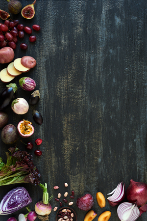 assortment: Collection of fresh purple toned vegetables and fruits on dark rustic distressed background, eggplant, onion, plum, carrot, fig, aubergine, grapes, radishes, loose leaf lettuce, beans passionfruit, cherries Stock Photo