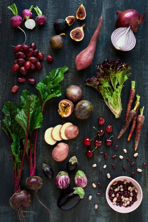 loose leaf: Collection of fresh purple toned vegetables and fruits on dark rustic distressed background, eggplant, beetroot, carrot, fig, aubergine, grapes, radishes, loose leaf lettuce, beans passionfruit, cherries