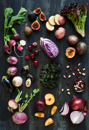 veggies: Collection of fresh purple toned vegetables and fruits on dark rustic distressed background, heirloom eggplant, fig, aubergine, cherries, radishes, lettuce, beans passionfruit, cabbage, plum, onion