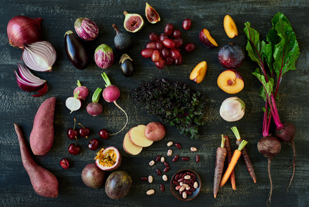 heirloom: Collection of fresh purple toned vegetables and fruits on dark rustic distressed background, heirloom carrots, beetroot, fig, aubergine, grapes, radishes, loose leaf lettuce, kale, beans passionfruit, cherries, sweet potato