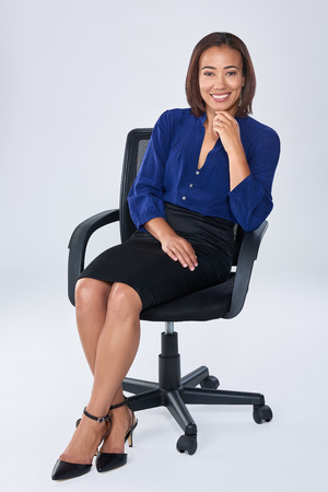 sits on a chair: Successful business executive sits on office chair smiling, happy having job satisfaction Stock Photo