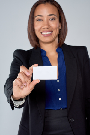 mixed race: Happy mixed race business woman holding up a blank card Stock Photo