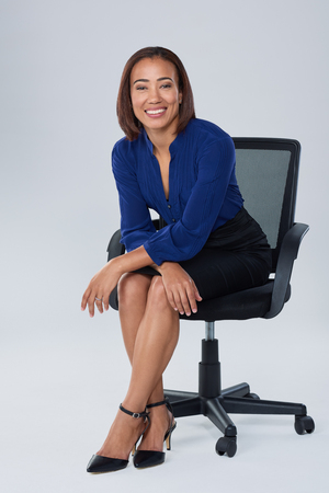 job satisfaction: Successful business executive sits on office chair smiling, happy having job satisfaction Stock Photo