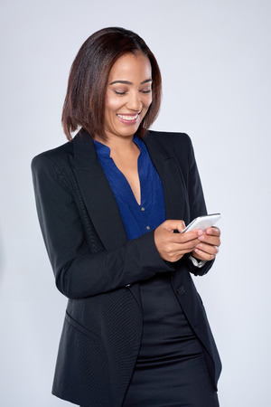 office attire: beautiful latino hispanic woman texting on her mobile cell phone smartphone in corporate office attire