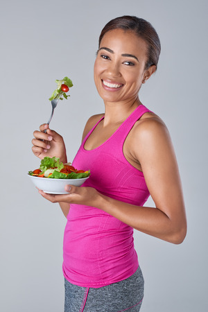 eating salad: Portrait of a fit healthy asian indian woman eating a fresh green salad