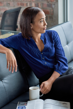 ponder: Casual portrait of businesswoman on couch having coffee, deep in thought