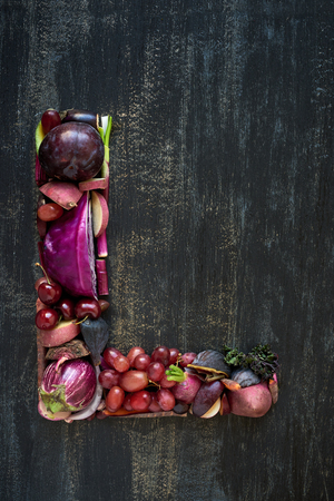 Alphabet letter made of purple vegetables and fruit on dark background Stock Photo