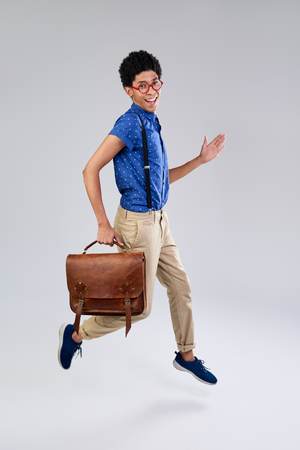 air movement: mixed race young man dressed as nerd geek jumping in mid air, movement isolated in studio