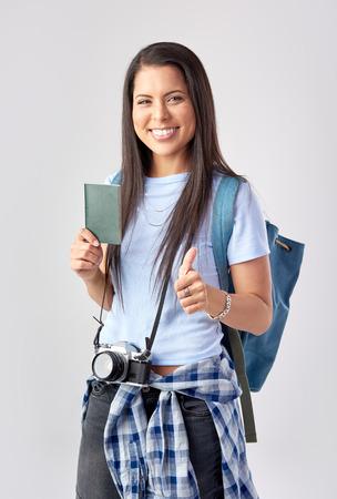 mochila de viaje: Mujer turística feliz con la cámara que sostiene el pasaporte en el estudio se va de vacaciones, aislado en gris