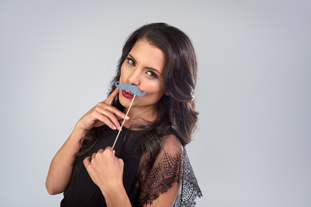 fake smile: Pretty glamourous woman posing with photobooth props fake mustache