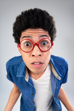 Funny portrait of young man with afro with eyes wide open, shocked facial expression in studio