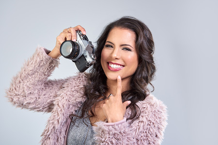 glamourous: Young beautiful woman in glamourous party clothes holding a vintage retro camera, taking photos Stock Photo