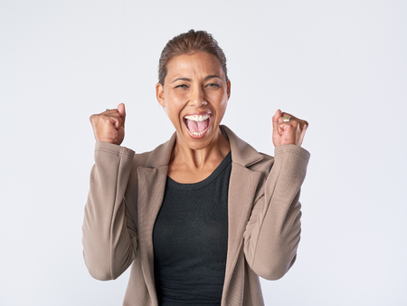 Real woman celebrating happy positive expression in studio isolated on grey
