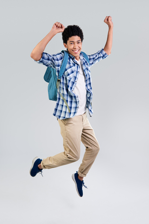 air movement: mixed race young man with backpack celebrating in mid air, movement jumping isolated in studio