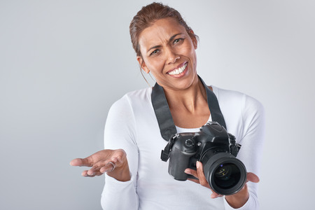 beginner: Middle aged woman holding dslr camera shrugging shoulders, beginner hobby