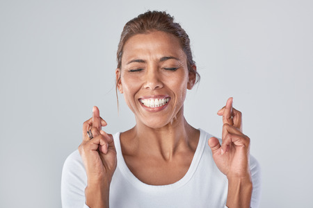 Headshot della donna razza mista desiderando sperando con le dita incrociate, espressioni Archivio Fotografico - 61268077