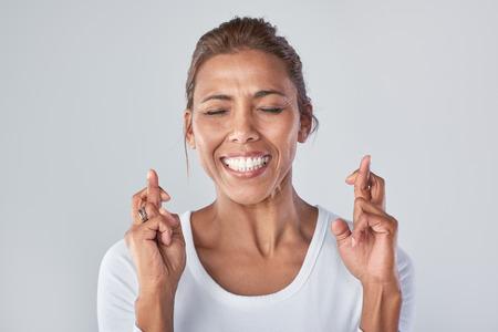 Headshot van gemengd ras vrouw die in aanmerking wensen te wachten met gekruiste vingers, uitdrukkingen