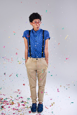 studious: Nerd geek studious young man partying with confetti suspenders and glasses spectacles Stock Photo