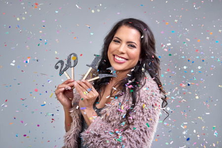 smiling happy mixed race woman in glamourous red lips celebrating at new years eve party with confetti falling