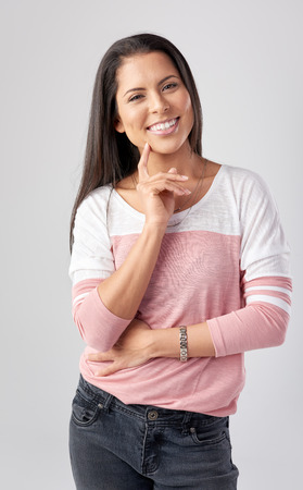 casual attire: Portrait of young mixed race woman in casual attire, isolated on grey in studio Stock Photo