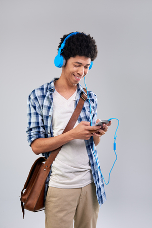 Happy smiling mixed race man listening to music, selecting songs on his mobile cell phone