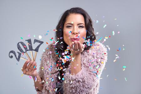 Docela glamour žena vítá nový rok 2017 fouká konfety do kamery, photobooth styl image Reklamní fotografie - 61471705