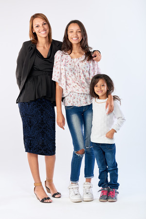 portait: mixed race woman family mom and daughters happy together posing for portait in studio isolated background