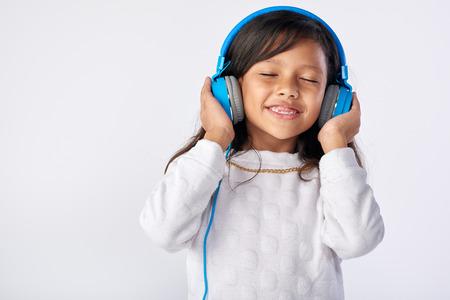 Jong meisje speelt haar favoriete nummer op de koptelefoon geïsoleerd in de studio Stockfoto - 63979361