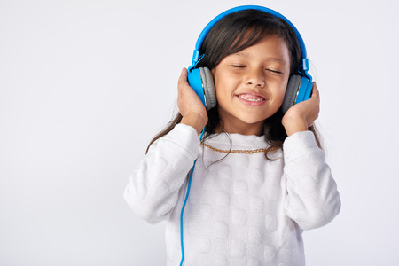 young girl playing her favorite song on headphones isolated in studio Banco de Imagens - 63979361