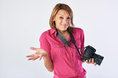 intimidated: Middle aged woman holding dslr camera shrugging shoulders, beginner hobby
