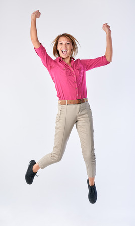 Full length portrait of mixed race woman celebrating with arms up isolated on grey