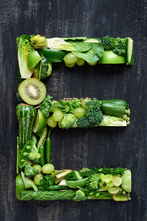 complete collection of alphabet letters made from healthy green fruit and vegetables on rustic distressed texture, overhead flat lay Stock Photo