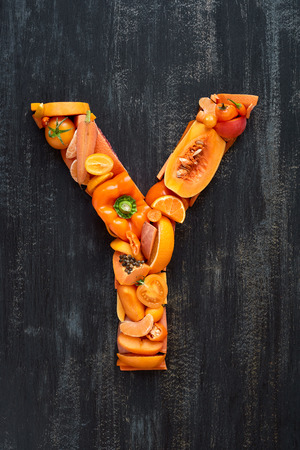 hued: orange hued collection of  raw produce shaped to letters of alphabet, poster design element