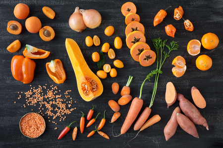Variety of raw orange coloured vegetables on dark rustic distressed background, part of a collection paw paw sweet potato chilli carrot apricot capsicum Banco de Imagens - 63982549