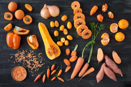 Verscheidenheid van rauwe oranje groenten op donkere rustieke noodlijdende achtergrond, onderdeel van een verzameling poot poot zoete aardappel chili wortel abrikoos capsicum