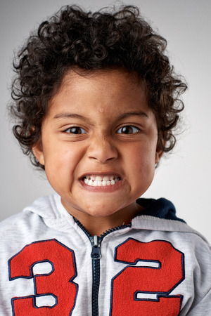silly face: Young boy making silly face portrait in studio