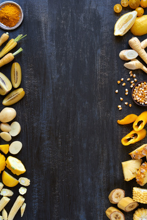 hued: Food background design with yellow hued fresh fruit and vegetables border frame shot overhead Stock Photo