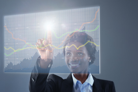 business trends: Smiling businesswoman looking at hologram financial graphs and stocks information analysing business information trends data Stock Photo