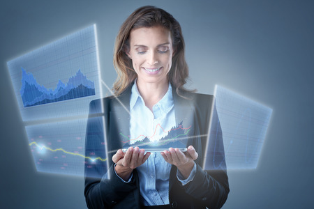 emitting: Mature businesswoman looking at holograms transmitted out of her tablet device, showing charts and business trends of stocks Stock Photo