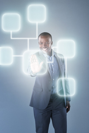 interconnected: Successful black businessman using futuristic hologram virtual interface display innovative modern technology Stock Photo