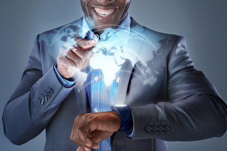 digital world: African man smiling while pressing smartwatch displaying globe hologram wearable technology futuristic business travel concept