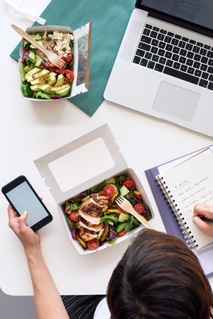 Overhead of busy working person at workstation with takeaway food and laptop, hands on phone