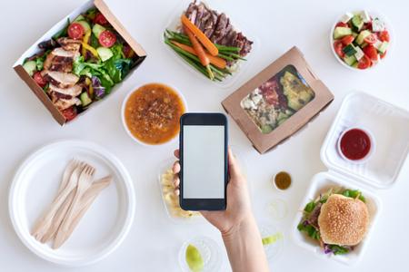 Mains tenant téléphone portable téléphone intelligent sur différents types de gourmet à emporter, livraison de nourriture pour le concept d'application de l'application
