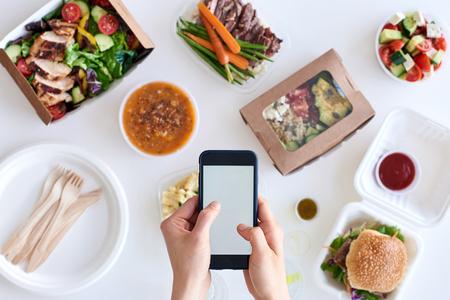 Manos que sostienen el teléfono móvil móvil smartphone a través de diferentes tipos de comida para llevar gourmet, la entrega de alimentos para la aplicación de conceptos de aplicaciones