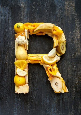 Flat lay series of organic yellow produce fruit and vegetables shaped into letters of alphabet, design element poster spelling layout