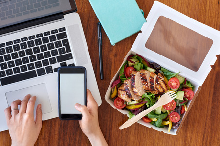 랩톱 컴퓨터에서 작업하고 모바일 휴대 전화 응용 프로그램 응용 프로그램에서 음식 주문