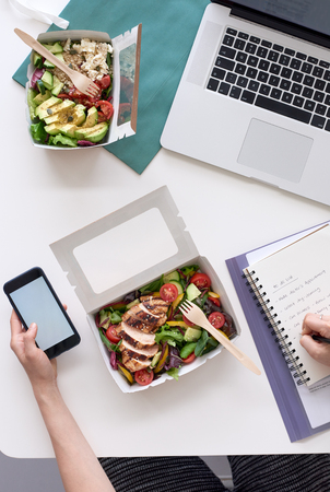busy person: Overhead of busy working person at workstation with takeaway food and laptop, hands on phone